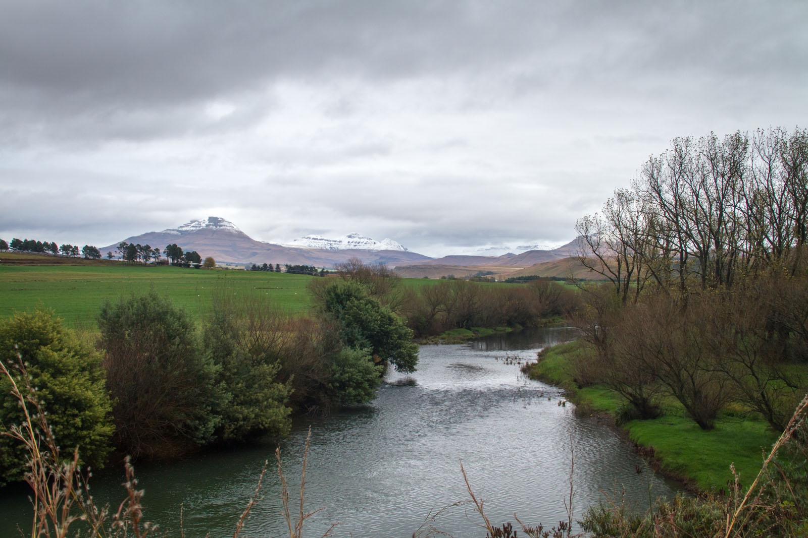 View of the snow capped mountains towering above Sinister Pool on the Umzimkulu River, Underberg